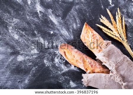 bread with wheat ears on dark board with flour, top view