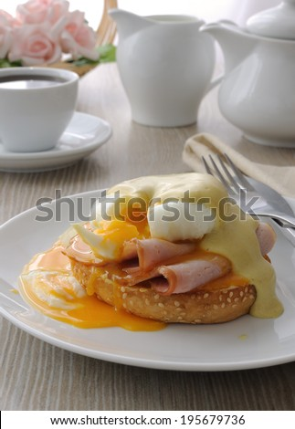 Breakfast of boiled eggs (poached) with ham on a bun mustard sauce  - stock photo