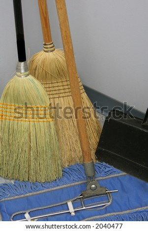 """Broom Closet"" Brooms standing against the wall in a broom closet. - stock photo"