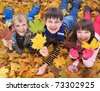Brothers and sister playing outside in Autumn leaves. - stock photo
