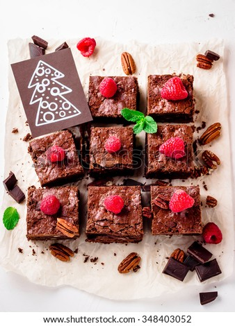 Brownie pieces with nuts decorated with berries and mint leaves, christmas card on the white paper. Selective focus. - stock photo