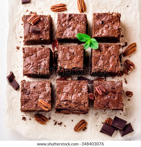 Brownie pieces with nuts on the white paper decorated with mint leaves. Selective focus. - stock photo