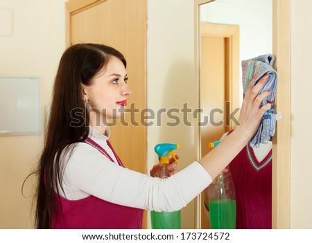 brunette girl cleaning  mirror indoor  - stock photo