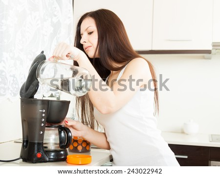 Brunette in  kitchen with  coffee maker - stock photo