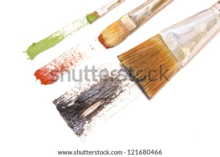 3 brushstrokes.Artists brushes, thin, medium, wide bristles paint wide green, red, and black brush strokes across bright white paper.Horizontal view.Isolated on a white background.Abstract concept. - stock photo