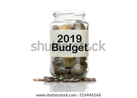 """2019 Budget"" text label on full coins of jar spill out from it isolated on white background - saving, donation, financial, future investment and insurance concept - stock photo"