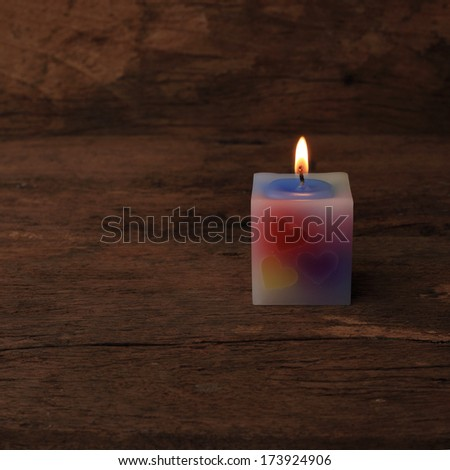burning candle standing on wooden table. - stock photo