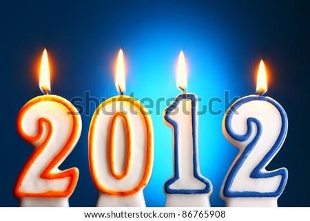 2012 burning candles close-up over blue backgroumd - stock photo