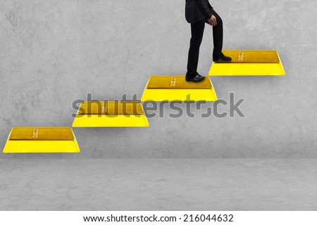 business man walking up gold bars stepping ladder idea concept for success and growth - stock photo