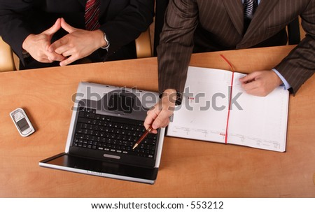 2 business men working at the desk with laptop and cell phone on