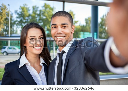 business people taking selfie and looking at mobile phone - stock photo