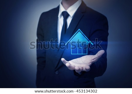 Businessman hand holding house, business property insurance concept