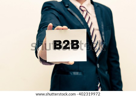 Businessman holding a card with text B2B  ,  business and technology concept. - stock photo