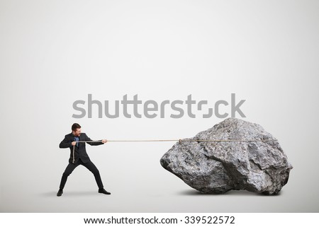 businessman in formal wear pulling the big stone over light grey background
