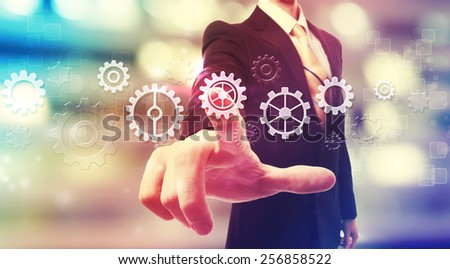 Businessman pressing gear icons over blurred city background - stock photo