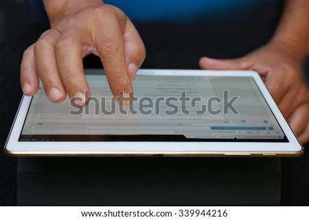 businessman use tablet, white tablet with a blank screen in the hands on wooden table, reading news and business data information. internet network communication.