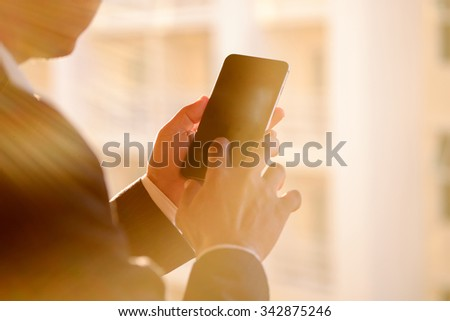 Businessman using a touch screen smart phone, vintage colours effect. - stock photo