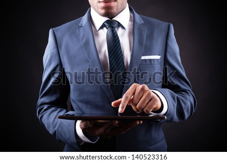 Businessman working on a digital tablet against black background - stock photo