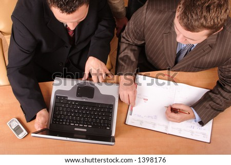 2 businessmen with laptop and calender sitting at the desk are planning - stock photo