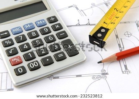 calculator and pencil and measuring tape on plans - stock photo