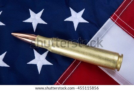 50 caliber brass bullet on American flag with room for your type.. - stock photo