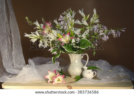 Campanula and lilies in a white vase .A still life of flowers . - stock photo