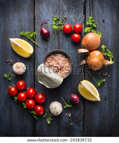 canned  tuna fish and ingredient for tomato sauce with herb, spices and lemon on blue wooden background, top view - stock photo