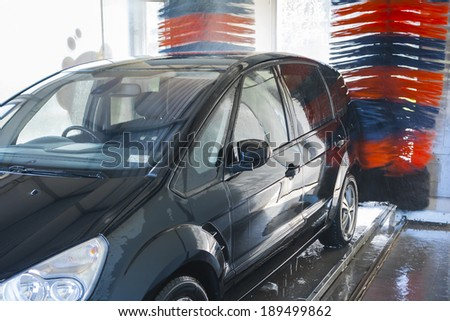 Car wash, black car in automatic car wash, rotating red and blue brush. Washing vehicle.  - stock photo