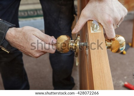 Carpenter Change door, Installing new door knob with lock, close-up human hend hold door handle. - stock photo