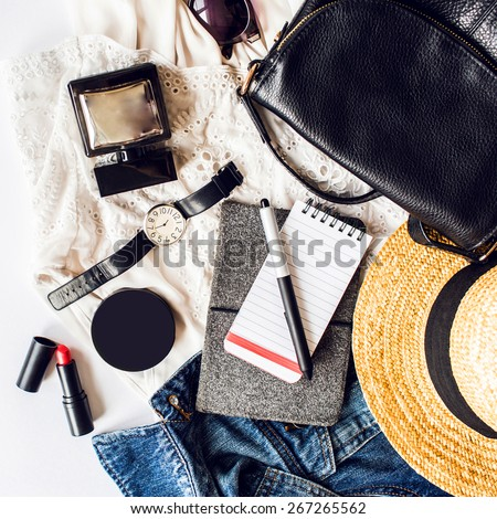 Casual  trendy outfit of young stylish woman. Essentials for modern   lady. Jeans jacket , note book,  white dress ,lipstick,powder, pen, leather bag, straw hat, perfume . - stock photo