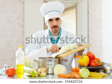 caucasian cook does veggie lunch at kitchen - stock photo