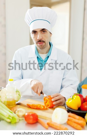 caucasian cook in uniform does veggy lunch - stock photo