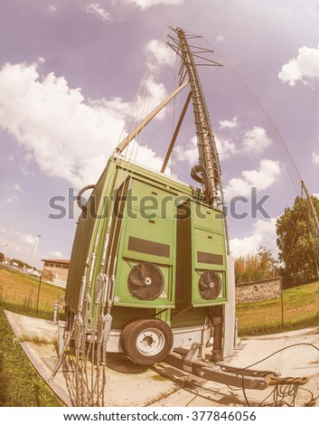 Cell on wheels aka COW mobile cell site with cellular antenna tower and electronic radio transceiver equipment part of a cellular network in a rural area seen with fisheye lens vintage