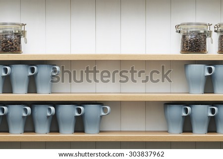 ceramic cups on the shelves in front of white wall.