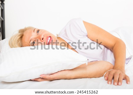 Cheerful mature lady in shirt awaking on bed at bedroom - stock photo