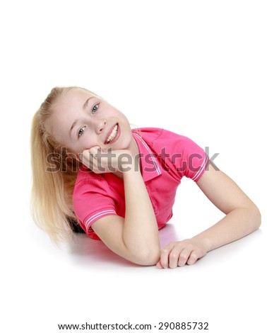 Cheerful teen girl in a pink shirt lying on the floor leaning on the arm- isolated on white background - stock photo