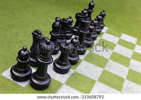 Chessboard and chess pieces on the grass in the garden,playing wooden chess pieces, business teamwork competition games concept, leadership hand of businessman
