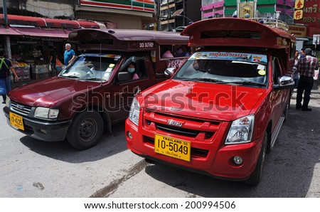 ChiangMai, Thailand - September 7 : Two-row  bus Red in ChiangMai, Thailand. September 7, 2013 Share taxi and popular transport in the streets of ChiangMai, waiting for tourists and customers