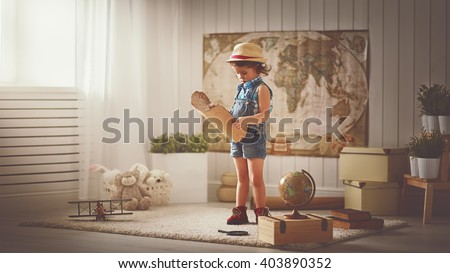 child girl at home dreaming of travel and tourism, exploring the world map and globe