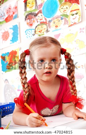 Child preschooler with colour pencil in playroom.