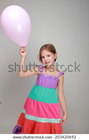 child with cute smile in a bright sundress holding colorful balloons on a gray background