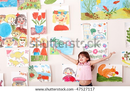 Child with hand up and picture  in playroom. Preschool. - stock photo