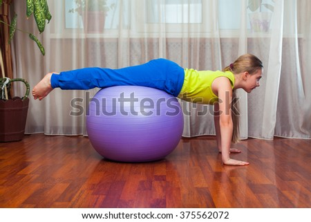 Child  with  on the ball for fittnesa at home  - stock photo