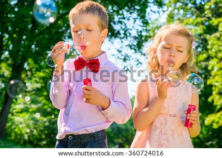 children at the celebration with soap bubbles on a summer day - stock photo