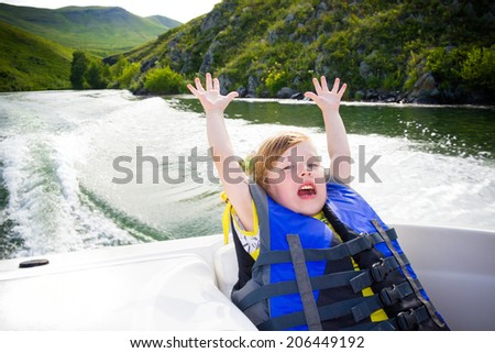 children by the boat on the river in a sunny day. - stock photo