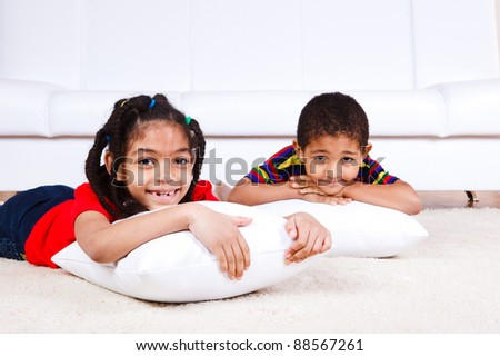 children  lying with pillows on the floor - stock photo