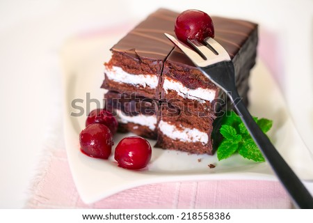 Chocolate cake with cherries on a plate - stock photo