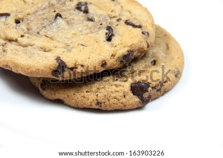2 chocolate chip cookies stacked on a white background - stock photo