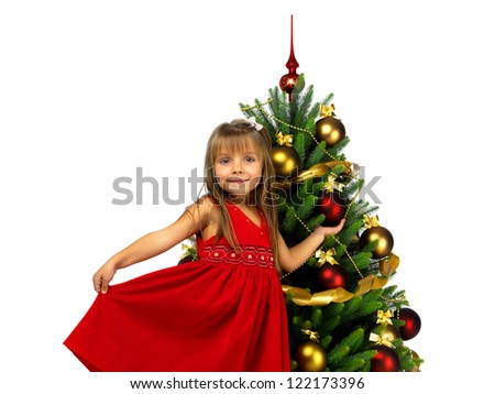 Christmas tree and Pretty little girl smiling with present - stock photo