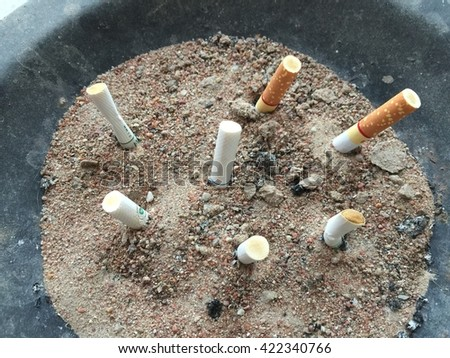 Cigarette on Ashtray with cigarette stubs - stock photo